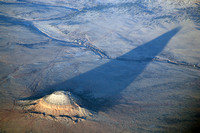 A solitary butte in Arizona casts a long late-day shadow.
